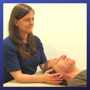 A craniosacral therapist holding a client's head